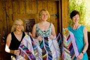 Winner Nemaiah Shaw (centre) receives the quilt from Kathy Moore (left) and Jan Micklethwaite (right).